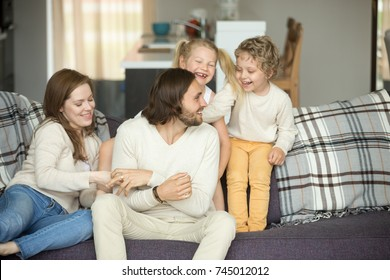 Cozy warm loving caring family of four at home together, happy parents and kids laughing having fun sitting on sofa, young married couple playing with preschool smiling son and daughter on couch