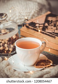 Cozy warm tea with books and glasses in winter
