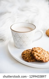Cozy weekend breakfast with fur blanket, cup of coffee and cookies on ceramic tray