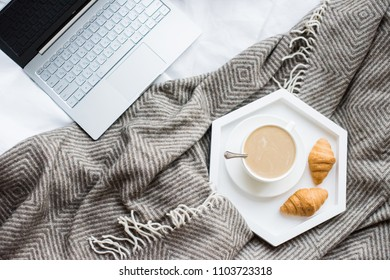 Cozy weekend at home, laptop and coffee in bed