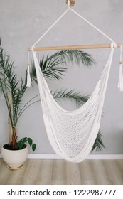 Cozy white hammock in living area, relaxing corner  at home. Minimal home interior design.