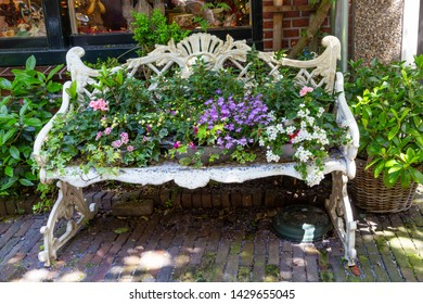 Cozy white renaissance bench loaded with colorful blooming plants Concept: city temperature or water management and control