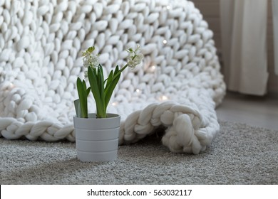 Cozy white scandinavian bedroom interior. Beautiful merino woolen plaid decorated bed and floor, super chunky yarn knitted blanket
