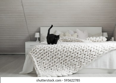 Cozy white scandinavian bedroom interior. Beautiful merino woolen plaid decorated bed and floor, black cat enjoying warm soft knit blanket.