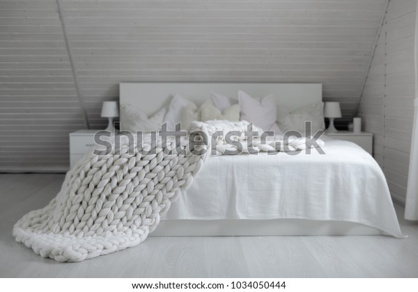 Cozy white scandinavian bedroom interior. Beautiful merino woolen plaid decorated bed and floor, super chunky yarn knitted blanket, nobody