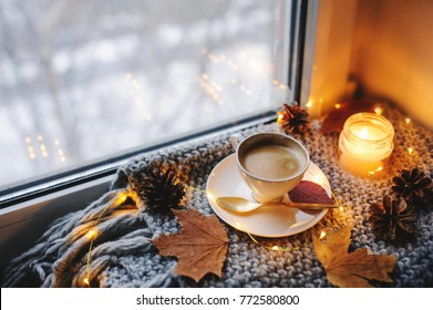 cozy winter or autumn morning at home. Hot coffee with gold metallic spoon, warm blanket, garland and candle lights, swedish hygge concept.