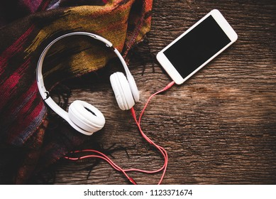 Cozy winter background, cup of hot coffee with marshmallow and headphone music, warm knitted sweater, vintage tone. Lifestyle and music concept