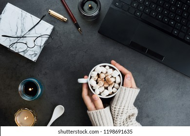 Cozy winter business flatlay arrangement with black laptop, women hands with vegan cocoa and candles on dark marble background