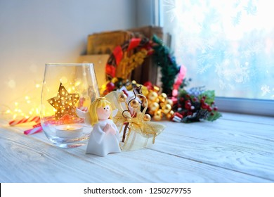 cozy winter composition with christmas angel and festive decor on the windowsill.  winter holiday season