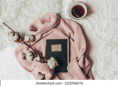 Cozy winter composition. Pink Knitted Sweater and cup of black tea on white background. Top View. Flat Lay. Copy Space