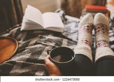 gemütlicher Wintertag zu Hause mit Tasse heißen Tees, Bücher und warmen Socken. Wochenende im Bett, Saisonurlaub und Überschwemmungskonzept