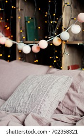 cozy winter decor with lanterns and garlands in the loft interior bedroom
