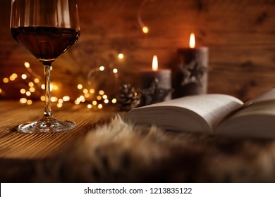 Cozy winter evening with a glass of red wine and a book by candlelight