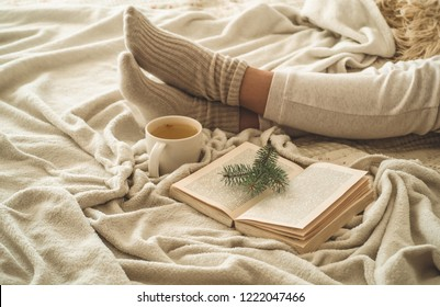 Cozy winter evening , warm woolen socks. Woman is lying feet up on white shaggy blanket and reading book. Cozy leisure scene. Text in book is unreadable. Woman relaxing at home. Comfy lifestyle.
