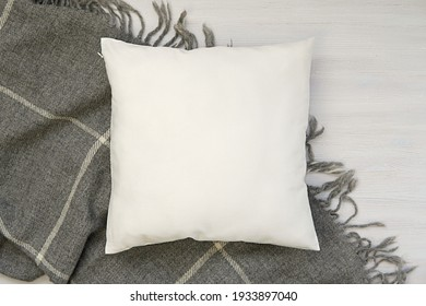 Cozy winter flat lay composition with white blank pillow and warm wool blanket, square pillow case, cushion mockup.