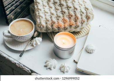 Cozy winter home interior with knitted blanket and candle