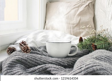 Cozy winter morning breakfast in bed still life scene. Steaming cup of hot coffee, tea standing near window. Christmas concept. Pillows, pine cones, gypsophila and fir tree branch on wool plaid.