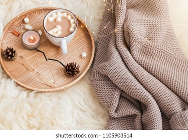 Cozy winter morning at home. Cocoa with marshmallows, knitted sweater and other seasonal accessories.
