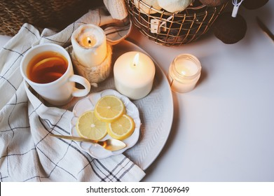 Cozy winter morning at home. Hot tea with lemon, candles, knitted sweaters in basket and modern metallic interior details. Still life composition, danish hygge concept