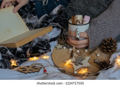 Cozy winter morning at hone with cup of hot cacao with marshmallows, interesting book and blanket. Hygge home interior.