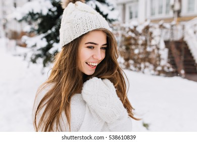 Cozy winter portrait of fashionable joyful young woman with long brunette hair walking on street full with snow. Surprised true positive emotions, warm white woolen gloves, knitted hat