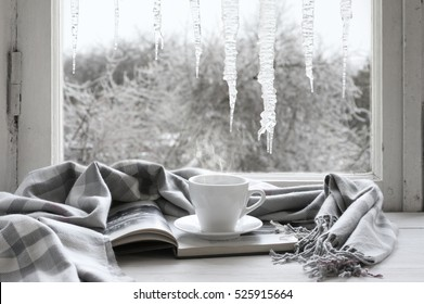 Cozy winter still life: cup of hot coffee and opened book with warm plaid on vintage windowsill against frozen big icicles from outside..