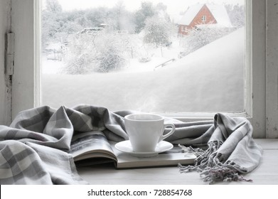 Cozy winter still life: cup of hot coffee and opened book with warm plaid on vintage windowsill of cottage against snow landscape with snowdrift from outside.