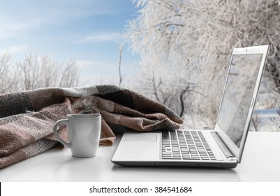Cozy winter still life: laptop, cup of hot coffee and warm plaid on windowsill against snow landscape from outside.