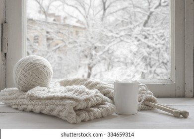 Cozy winter still life: mug of hot tea and warm woolen knitting on vintage windowsill against snow landscape from outside.
