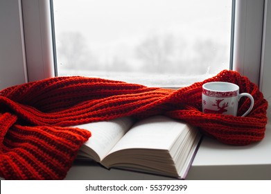 Cozy winter still life: mug of hot tea and opened book with warm plaid on modern windowsill against snow landscape from outside. Selective focus.