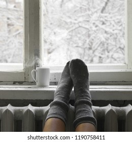 Cozy winter still life: woman feet in warm woolen socks and mug of hot beverage on old windowsill against snow landscape from outside.