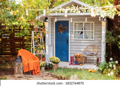 Cozy wooden house porch with chair, blanket, potted chrysanthemums and pumpkins. Decor outdoor of autumn yard. Facade House decorated for autumn holidays. Exterior autumn home. halloween. Autumn relax