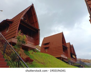 The cozy wooden lodges on a hill under cloudy sky