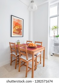 Cozy wooden table and chairs, picture frame in a spacious modern kitchen.
