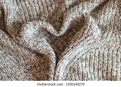 Cozy wool grey sweater for gorls and nice heart, stylish texture of clothes and modern background