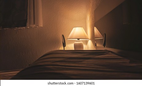 Cozy yellow light coming from the lamp during evening in the dark bedroom next to the bed making a romantic atmosphere for reading or relaxing