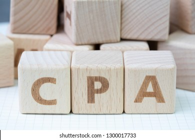 CPA, Certified Public Accountant or Cost per Action concept, cube wooden block building word CPA, certificate using for accounting audit or online advertising term for cost that paid per user action.