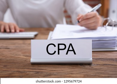 CPA Name Plate On The Desk With The Businesswoman Analyzing The Invoice In The Office