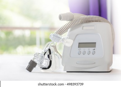 CPAP machine mask and tube on white bed cover in bedrooom blurred purple curtain background.  CPAP machine components.Obstructive sleep apnea therapy.