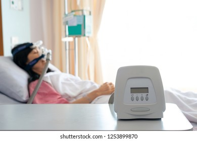 Cpap machine is treating senior patient woman wearing Cpap mask sleeping smoothly without snoring in hospital room.
