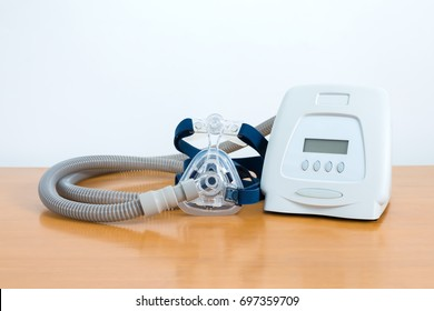 Cpap system includes of cpap machine,mask,tube and headgear on wooden table,front view white background.Full components of Cpap machine .
