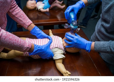 CPR practitioner examining airway passages on infant dummy. Model dummy lays on table and two doctors practice first aid.