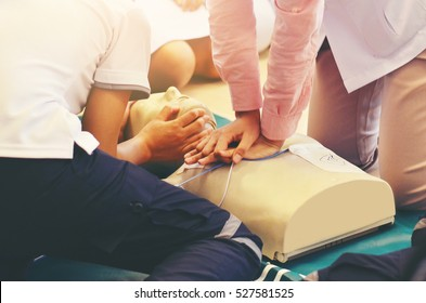 CPR training medical procedure - Demonstrating chest compressions on CPR doll in the class