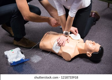 CPR training medical procedure workshop. Demonstrating chest compressions and use of AED automatic defibrillator on CPR doll.