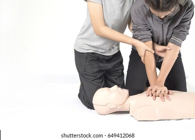 CPR training medical procedure,Demonstrating chest compressions on CPR doll in the class,White background