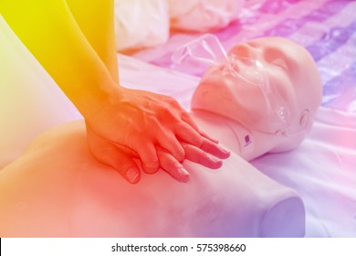 CPR training using and an adult training manikin sweet color on soft light pink purple color background