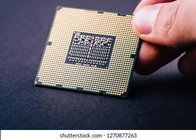 CPU processor chip computer on dark black background holding in hand
