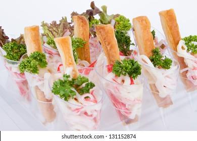 Crab and bread sticks in a plastic cone.