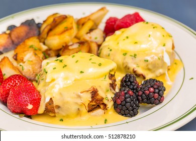 Crab cake eggs benedict served with berries and german potatoes