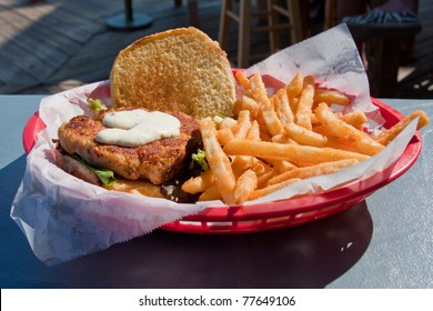 Crab cake sandwich with french fries in a basket